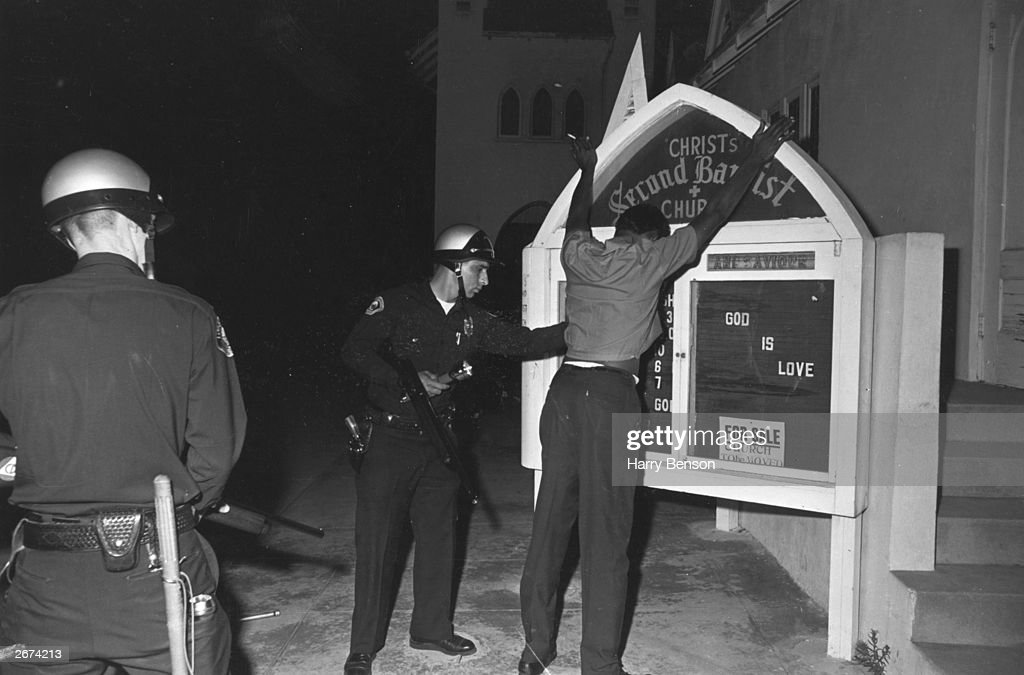 A suspect being searched by two armed police during the Watts race riots in Los Angeles, California, 11th-15th August 1965.