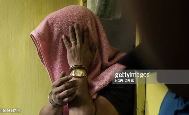 A suspect covers his face after a drug raid conducted by police in Manila on February 8 2018 Philippine President Rodrigo Duterte's war on drugs has...