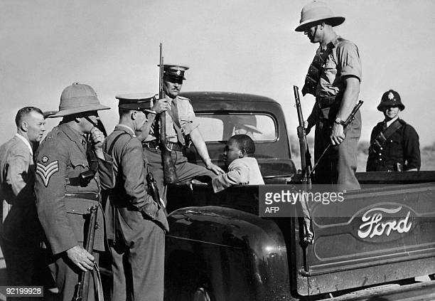 A suspect is arrested and kept in a Ford police car as violence increased in East London in Novemebr 1952