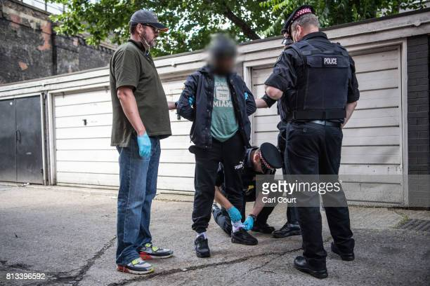 A suspect is detained and searched by police officers after being arrested for alleged possession of a dangerous weapon near Elephant and Castle...