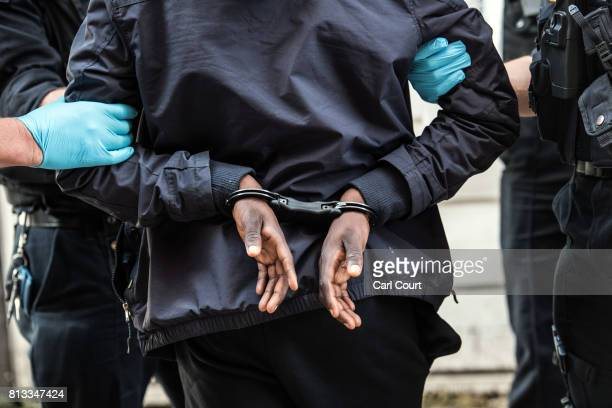 A suspect is detained by police officers after being arrested for alleged possession of a dangerous weapon near Elephant and Castle Station during...