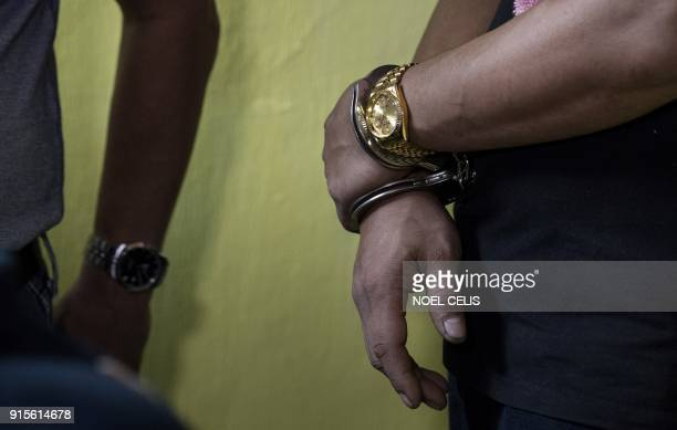 A suspect is handcuffed after a drug raid conducted by police in Manila on February 8 2018 Philippine President Rodrigo Duterte's war on drugs has...