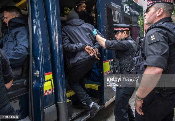 A suspect is taken to a waiting police van after being arrested for alleged possession of a dangerous weapon near Elephant and Castle Station during...