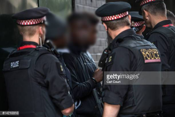 A suspect looks on after being detained and searched by police officers after being arrested for alleged possession of a dangerous weapon near...