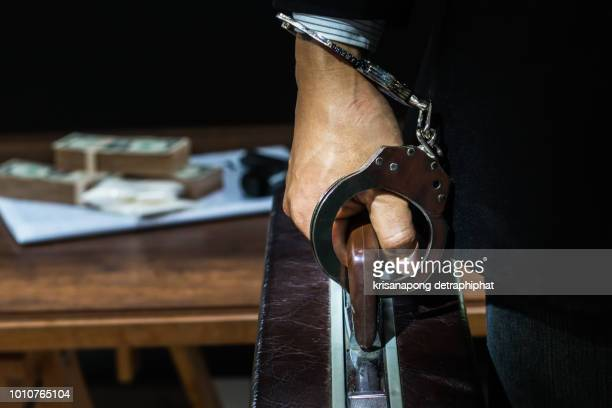 suspect or criminal man with handcuffs being interviewed by detectives in interrogation room a suspected drug trafficking - cocaine, heroin, spice, marijuana, and etc - 法的手続 ストックフォトと画像