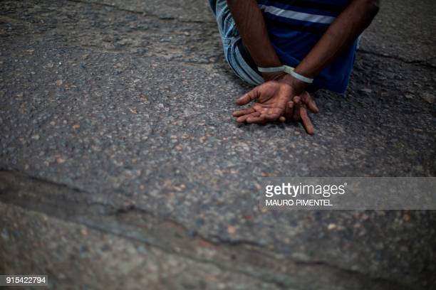 TOPSHOT A suspect remains handcuffed after being arrested by Rio's Civil Police during a joint operation at Cidade de Deus favela in Rio de Janeiro...