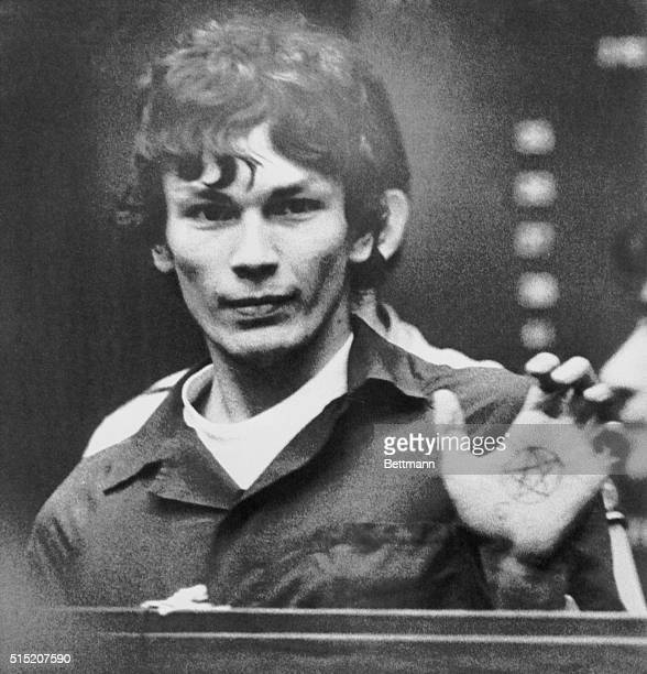 Suspect Richard Ramirez accused of being the Los Angeles area serial killer called the Night Stalker flashes his left palm showing a pentagram a...