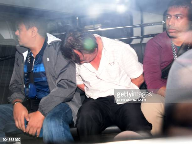 A suspect to be charged in court in the Shell Bukom fuel theft case arrives in a police van at the State court in Singapore on January 13 2018...