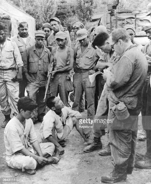 Suspected Communists captured near the lines are brought in for questioning, and later released during the Korean War.