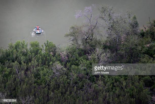 A suspected drug smuggling scout paddles his raft back across the Rio Grande into Mexico from the US side of the border on May 21 2013 near Hidalgo...