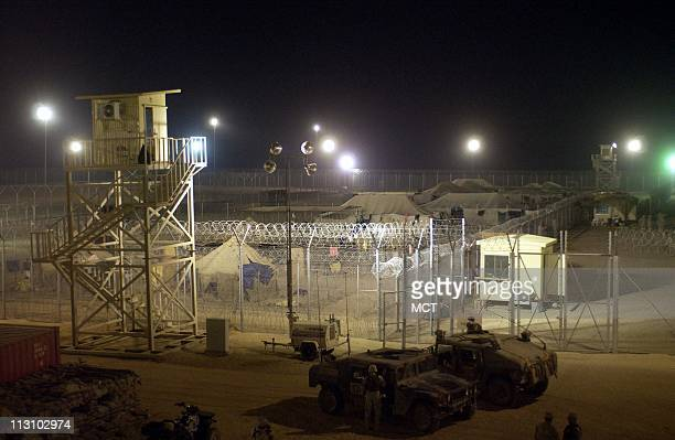 Suspected foreign fighters are kept behind razor wire and under the watch of armed military police at the Americanrun Camp Bucca detention center 300...