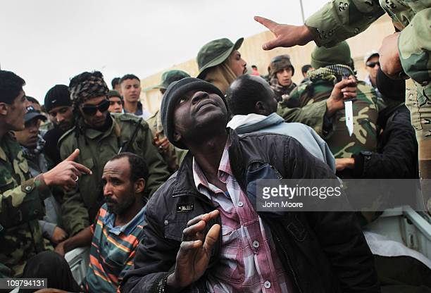 Suspected government agents cower from rebel militiamen after being captured on the frontline March 25 2011 in Ben Jawat, Libya. Opposition forces...
