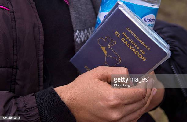 A suspected immigrant holds a passport from El Salvador after being detained by the US Border Patrol near the USMexico border in McAllen Texas US on...