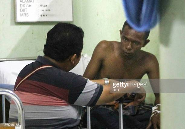 A suspected Indonesian boat crew member identified as Ronald of the capsized boat overloaded with asylum seekers is interrogated by police while...