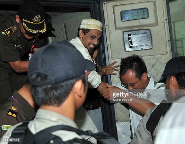Suspected Indonesian bombmaker Umar Patek gets out of a van as he arrives at the West Jakarta court prior to his trial in Jakarta on March 12 2012...
