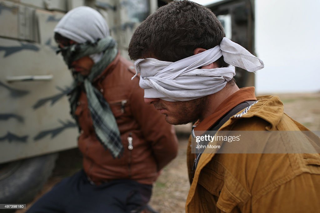 Suspected ISIL or Daesh are detained by Kurdish Peshmerga forces after they fled their frontline village to a Kurdish-controlled area on November 16, 2015 to Sinjar, Iraq. Peshmerga forces carefully screened displaced Iraqis as they arrived, fearing enemy infiltrators and suicide bombers. Kurdish forces, with the aid of massive U.S.-led coalition airstrikes, liberated Sinjar from ISIL extremists, known in Arabic as Daesh, moving the frontline south. About one thousand villagers in Ghabosyeh fled north to Kurdish held territory, to take refugee camps or onward as refugees to Turkey or Europe.