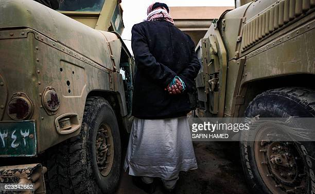 A suspected Islamic State group jihadist walks between two vehicles after his capture by Iraqi forces near the ancient town of Nimrud located 30...