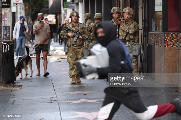 TOPSHOT A suspected looter carrying boxes of shoes run past National Guard soldiers in Hollywood California June 1 after a demonstration over the...