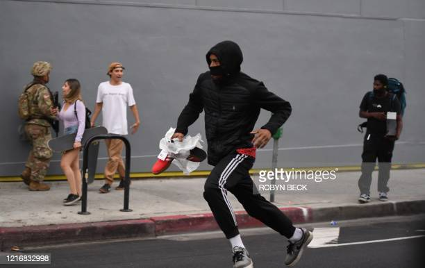A suspected looter carrying boxes of shoes run past National Guard soldiers in Hollywood California June 1 after a demonstration over the death of...