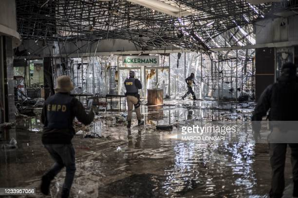 Suspected looter is fired upon with rubber bullets by Ekurhuleni Metro Police Department officers on patrol inside a flooded mall in Vosloorus, on...