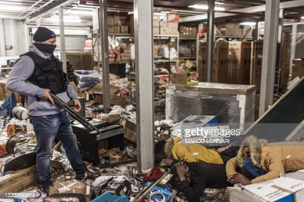 Suspected looters are pinned to the ground by an armed private security officer looking for looters, inside a flooded mall in Vosloorus, on July 13,...