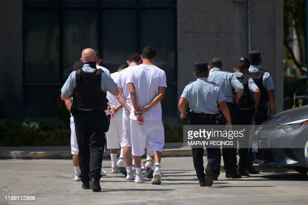 Suspected members of the Mara 18 who remain under custody, are escorted as they arrive at Isidro Menendez Justice Court in San Salvador, on February...
