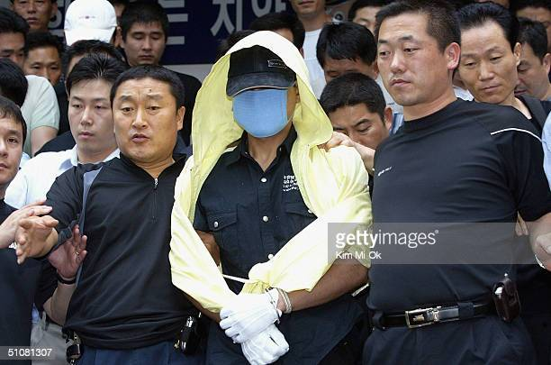 Suspected serial killer Yoo YoungChul is escorted by South Korean police during an inspection of suspected murder sites on July 19 2004 in Seoul...