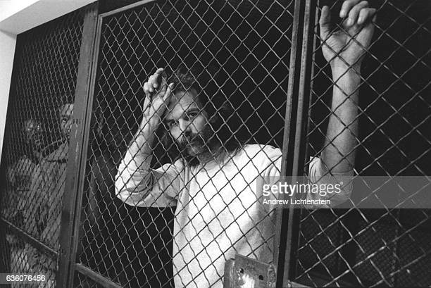 Suspected street dealers and their customers wait behind bars to be processed before being transferred to the city jail downtown, December 1, 1992....