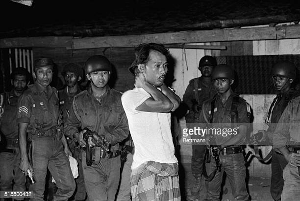 A suspected sympathizer with the Communistled abortive coup of October 1th is questioned under gunpoint The Indonesian Army is continuing its careful...