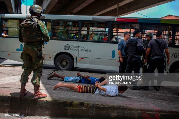TOPSHOT Suspects are detained and handcuffed by Rio's Civil Police during a joint operation at 'Cidade de Deus' favela in Rio de Janeiro Brazil on...