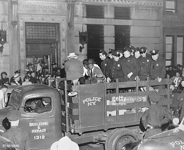 Suspects in a Harlem 'race riot' are herded to the front of a truck by a troupe of police as they are driven to jail