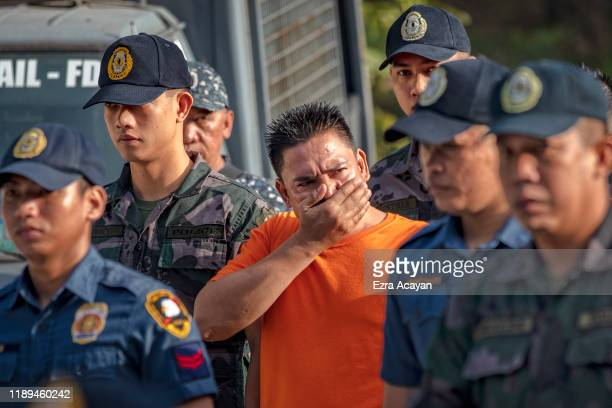 Suspects in the Ampatuan Massacre are escorted by policemen as they arrive at Camp Bagong Diwa where a court will issue a verdict on the crime on...
