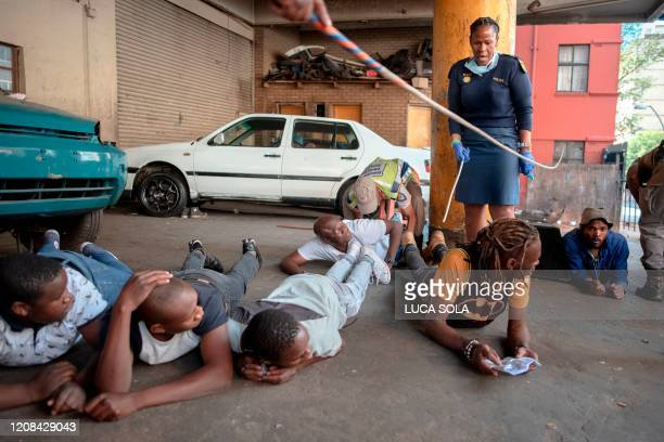 TOPSHOT Suspects lie on floor as a member of the South African Police Service arrests them because they defied the lockdown rules and was found with...