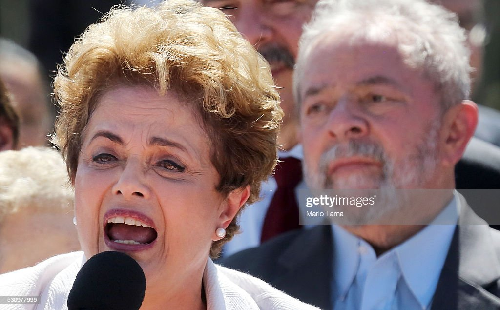 Suspended Brzilian President Dilma Rousseff (L) speaks to supporters as former President Luiz Inacio Lula da Silva (R) looks on at the Planalto presidential palace after the Senate voted to accept impeachment charges against Rousseff on May 12, 2016 in Brasilia, Brazil. Rousseff has been suspended from her presidential duties and will face a Senate trial for alleged manipulation of government accounts.