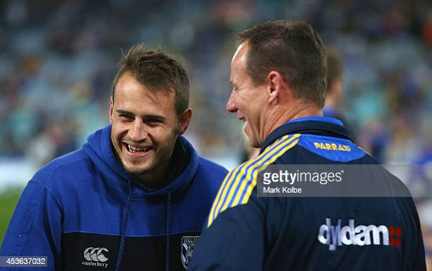 Suspended Buldogs player Josh Reynolds shares a laugh with a member of the staff as he watches on before the round 23 NRL match between the...