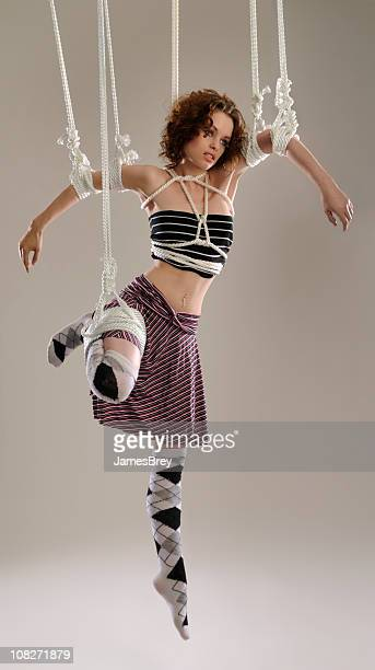 Suspended Fashion Model Puppet Hanging on White Ropes