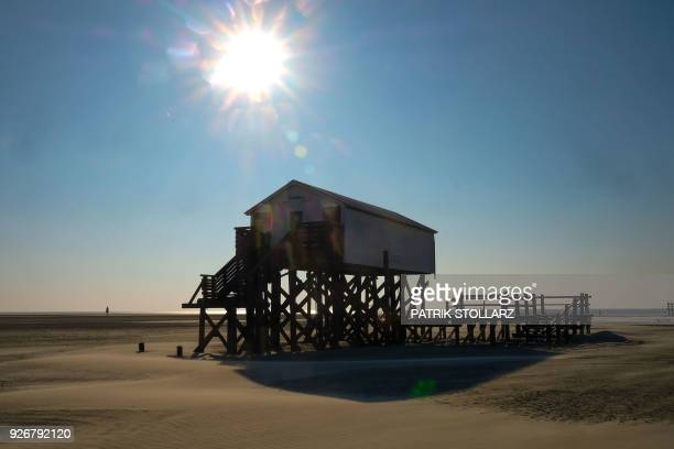 A suspended house is pictured at the beach in Sankt Peter Ording on the North Sea coast in northern Germany on March 3 2018 / AFP PHOTO / Patrik...