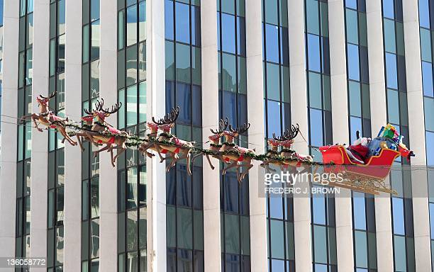 Suspended lifesize figures of Santa Claus delivering toys from in his sleigh being pulled by reindeer are seen against an office building on Wilshire...
