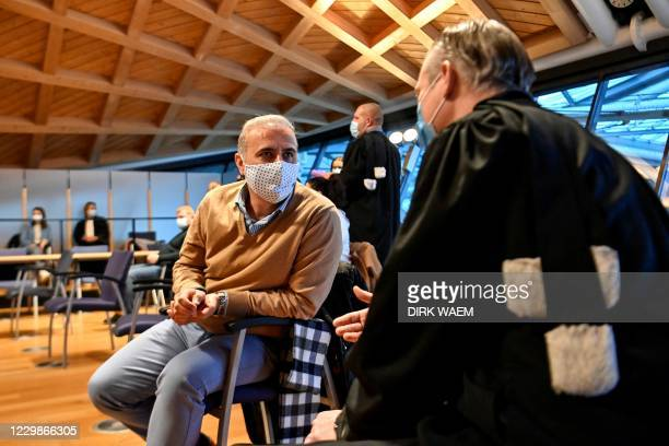 Suspended Mechelen city council member Melikan Kucam speaks with his lawyer ahead of his trial before Antwerp criminal court, along with nine other...