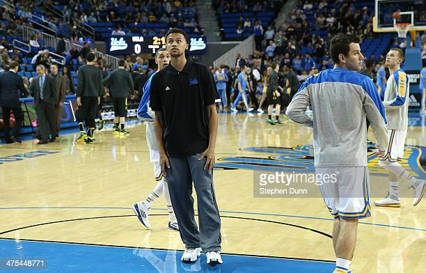 Suspended player Kyle Anderson of the UCLA Bruins stands on the court as his teammates warm up for the game against the Oregon Ducks at Pauley...