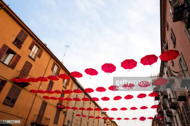 Suspended red umbrellas in Cuneo street