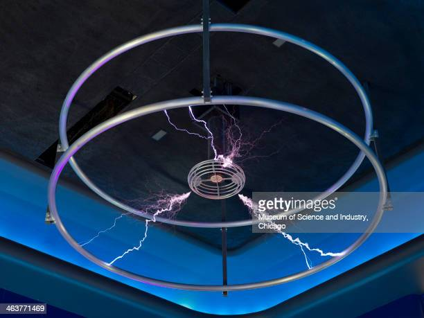 A suspended Tesla Coil with sparks of electricity similar to lightning contained within two parallel metal rings in the Science Storms exhibit at the...