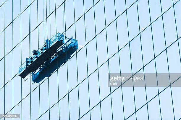suspended window cleaning platform on glass building - window cleaning stock photos and pictures