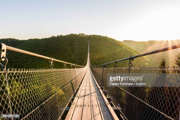 suspension bridge and mountain against sky - suspension bridge stock photos and pictures