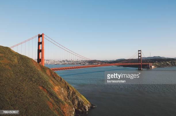 suspension bridge in city against clear sky - bortes bildbanksfoton och bilder