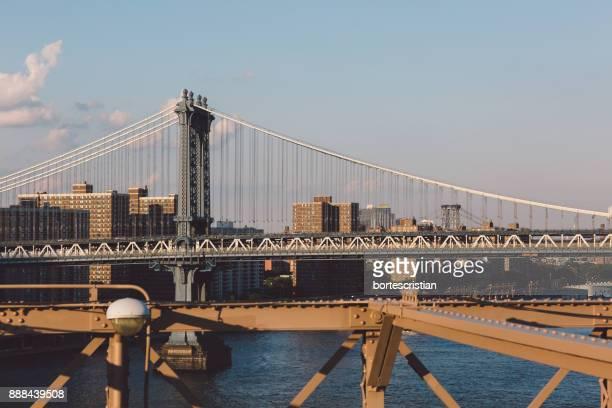 Suspension Bridge In City Against Clear Sky