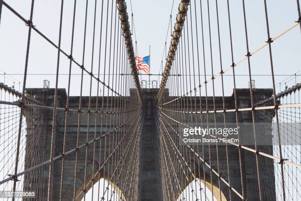 suspension bridge in city against sky - bortes stock pictures, royalty-free photos & images