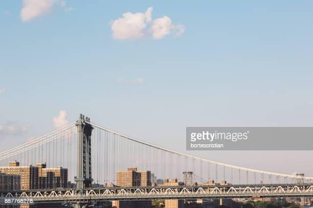 Suspension Bridge In City Against Sky