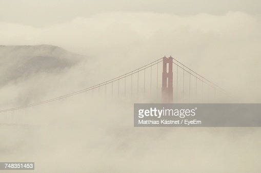 Suspension Bridge In Foggy Weather Against Sky
