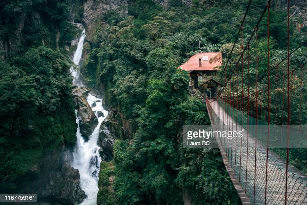 suspension bridge next to a waterfall in ecuador. - ecuador fotografías e imágenes de stock
